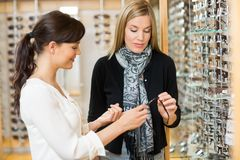 Woman And Customer Holding Glasses At Store Royalty Free Stock Images