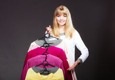 Woman customer holding hangers with clothes Royalty Free Stock Photos