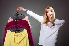 Woman customer holding hangers with clothes Stock Image