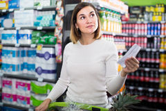 Woman customer looking at notes in shopping list. In supermarket Stock Photos