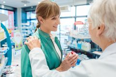 Woman customer in pharmacy buying drug hoping to get better. Being consoled by the chemist stock photography