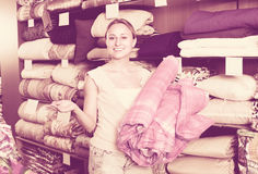 Woman customer picking blanket. Joyful smiling young woman customer picking bed blanket in textile department Stock Photo