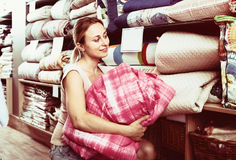 Woman customer picking blanket. Joyful smiling young woman customer choosing blanket in textile department Royalty Free Stock Photo