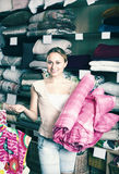 Woman customer picking blanket. Smiling young woman customer picking bed blanket in textile department Stock Images
