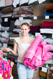 Woman customer picking blanket. Smiling young woman customer picking bed blanket in textile department Royalty Free Stock Photography