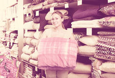 Woman customer picking blanket. Smiling young blonde woman customer choosing blanket in textile department Stock Photo