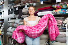 Woman customer picking blanket. Smiling young blonde woman customer selecting  blanket in textile department Royalty Free Stock Photo