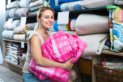 Woman customer picking blanket. Smiling young woman customer choosing blanket in textile department Royalty Free Stock Photos