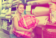 Woman customer picking blanket. Smiling young woman customer choosing blanket in textile department Stock Photography