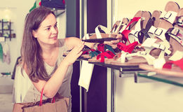 Woman customer selecting shoes in footgear center. Portrait of woman customer selecting shoes in footgear center Royalty Free Stock Photography