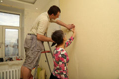 Woman customer and the worker putting up wallpaper stock images