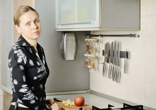 Woman cut an apple in the kitchen Stock Images