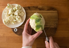 Woman cut cauliflower on cutting board on kitchen table Royalty Free Stock Images