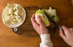 Woman cut cauliflower on cutting board on kitchen table Royalty Free Stock Photography