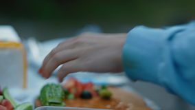 Woman cut  cucumber on the picnic. Outdoor stock footage