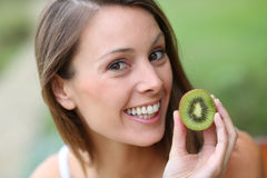 Woman with a cut kiwi Royalty Free Stock Photography