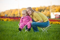 Woman and cute baby sitting on chairs in park Stock Images