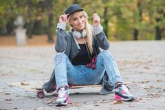 Woman with a cute smile sitting on skate board Royalty Free Stock Image