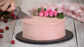 Woman cuts a beautiful cake with roses. Sweet food.  stock video