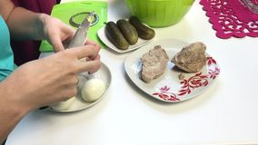 Cooking meat salad with eggs, potatoes, cucumbers and peas. Woman cuts boiled eggs in a container with other ingredients. Cooking meat salad with eggs, potatoes stock video