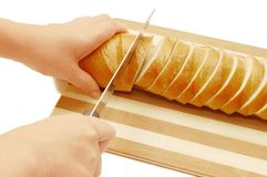 Woman cuts bread on a board Royalty Free Stock Photo