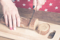 Woman cuts bread on a cutting board Stock Photo
