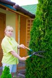 Woman cuts bush Royalty Free Stock Images