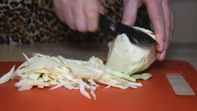 A woman cuts cabbage on a cutting board.