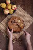 The woman cuts a charlotte with apples Stock Photos