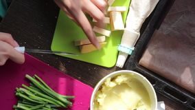 Woman cuts cheese on a cutting board. Next to other ingredients for cooking dinner. Mashed potatoes, fresh onion feathers. stock footage
