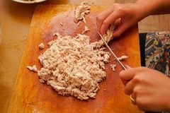 Woman Cuts chicken meat into pieces. Woman Cuts chicken meat into small pieces stock photography