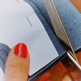 Woman cuts fabric with scissors. Home clothes business.  royalty free stock photos