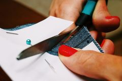 Woman cuts fabric with scissors. Home clothes business.  stock photo