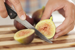 Woman cuts fig on cutting board in kitchen Stock Image