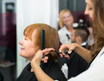 Woman cuts hair  at the barbershop Stock Photos