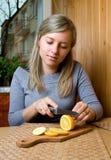Woman cuts lemon. Pretty woman cuts lemon in kitchen Royalty Free Stock Images
