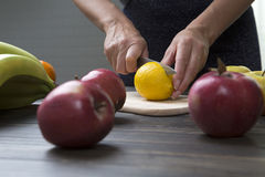 Woman cuts a lemon with a knife. Stock Images