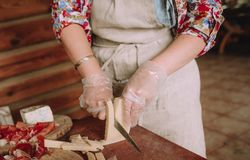 Woman cuts meat hard cheese lobules board. Woman cuts meat and hard cheese with lobules on a wooden board royalty free stock photos