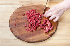 Woman cuts meat on wooden cutting board Royalty Free Stock Images