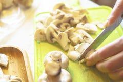 Woman cuts mushrooms. Chopped mushrooms on a green plastic tray stock image