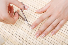 Woman cuts nails scissors Stock Image