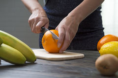 Woman cuts an orange with a knife. Royalty Free Stock Photos