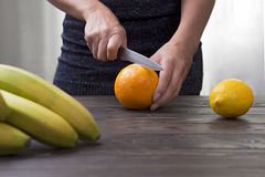 Woman cuts an orange with a knife. Stock Photos
