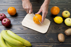 Woman cuts an orange with a knife. Royalty Free Stock Photography