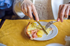 Woman cuts the pizza with cheese and ham Royalty Free Stock Photos