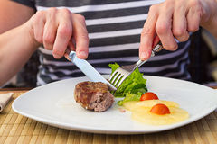 Woman cuts pork tenderloin medallions Royalty Free Stock Photos
