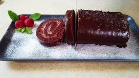 Woman cuts on slices chocolate roll on the kitchen. Swiss roll on the plate stock video footage