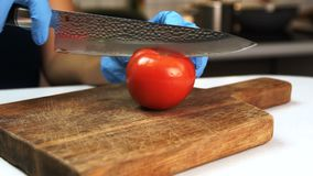Woman cuts tomato in half with knife in kitchen of house. She puts red ripe fruit on wooden board and cuts it into two pieces slowly using acute steel chopper stock footage