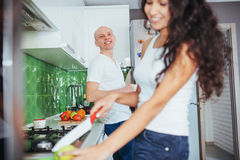 Woman cuts vegetables together in the kitchen Stock Photos