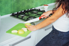 Woman cuts vegetables together in the kitchen Royalty Free Stock Photography